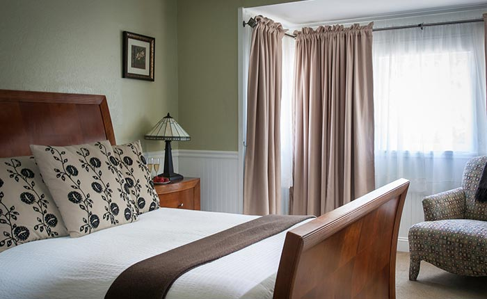 King bed with wooden headboard and wooden side table and cream colored curtains in the Helena room of the Craftsman Inn in Calistoga, CA, in the Napa Valley Wine Country