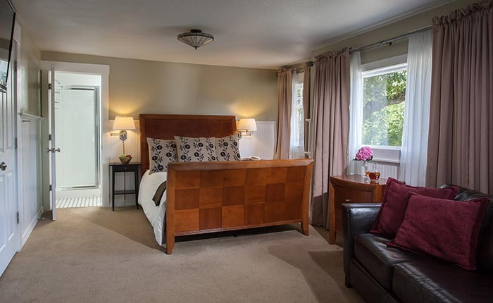 Queen bed and black leather couch and large window in the Howell Room at the Craftsman Inn in Calistoga, CA, in the Napa Valley Wine Country