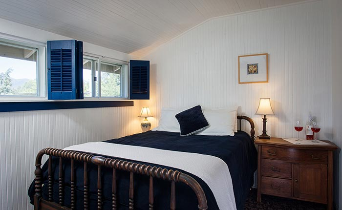 Blue blanket, cushion, and wood paneled blinds with wooden side tables and lamps in the Napa room in the Calistoga Wine Way Inn in the Napa Valley Wine Country