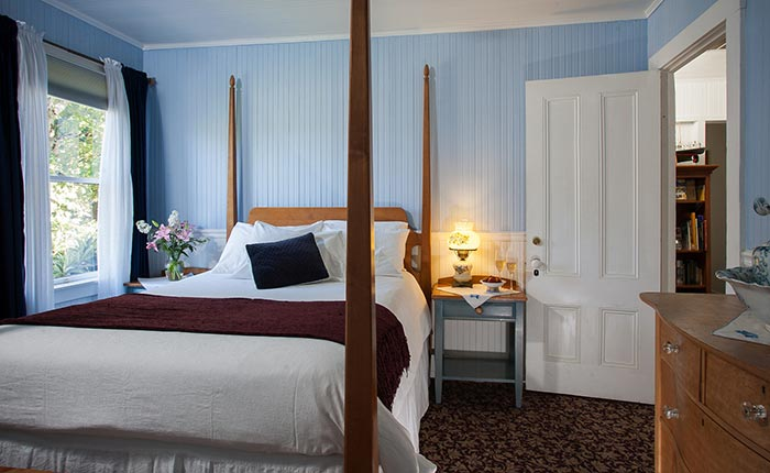 A view of the interior of four poster bed, wood side table, blue curtains, and pink flowers in a vase in the Rutherford Room at the Calistoga Wine Way Inn in the Napa Valley Wine Country