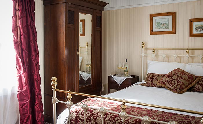 Gold trimmed queen bed frame with burgundy cushions and blanket and wooden wardrobe and side table and lamp in the St. Helena room  in the Calistoga Wine Way Inn in the Napa Valley Wine Country