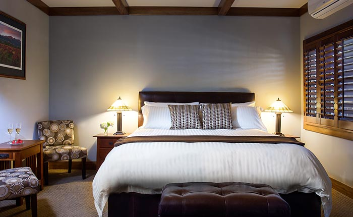 King size bed with cushions, bedside table, two chairs and side table in the Silverado room at the Calistoga Wine Way Inn in the Napa Valley Wine Country