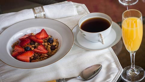 A delicious breakfast of granola and fruit with coffee and orange juice