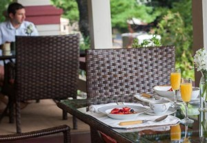 Breakfast of coffee, mimosas, and a bowl of fruit on patio table with chairs and cushions of the Craftsman Inn in Calistoga, CA, in Napa Valley Wine Country