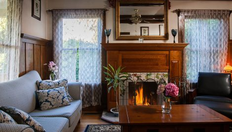 Living room of the Wine Way Inn with coach, armchair, coffee table, flowers, and fireplace in Calistpga, CA; Napa Valley, Wine Country