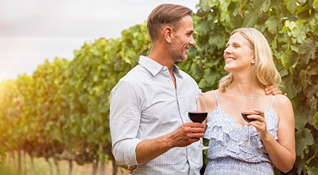 Couple wine tasting in the Napa Valley holding red wine glasses in front of a vineyard experiencing the Wine and Dine Package