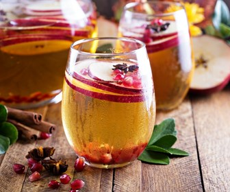 Fruit cocktails in stemless wine glasses with apple, pomegranate, and cinnamon in glasss and on wooden table