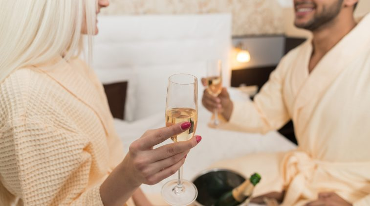 Couple in robes on bed cheers champagne in Napa Valley Wine Country