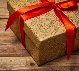 Golden present wrapped in red ribbon on wooden table