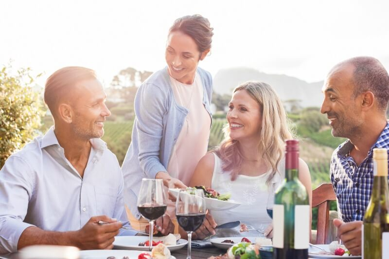 people at dinner party with wine