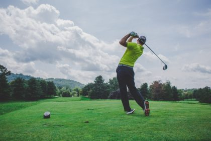 A man swings a golf club on a bright green, under a sky of scattered clouds.