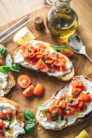 An spread of bruschetta with colorful tomatoes and a small jar of olive oil.