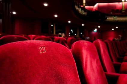 A dark theater with bold, red velvet seats.
