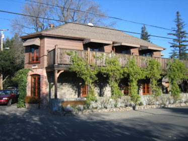 The outside view of the French Laundry, including stonework, siding, and a balcony with green vines growing along it.