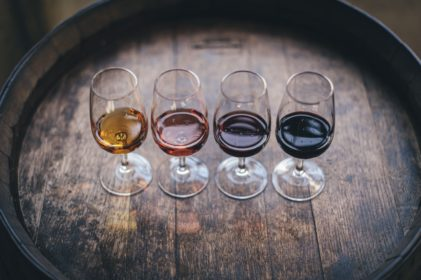 Four wine glasses filled with different wines, sitting atop a wine barrel.