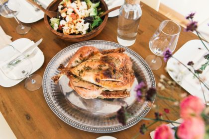 A table setting with a roasted chicken at the center and purple and pink flowers nearby.